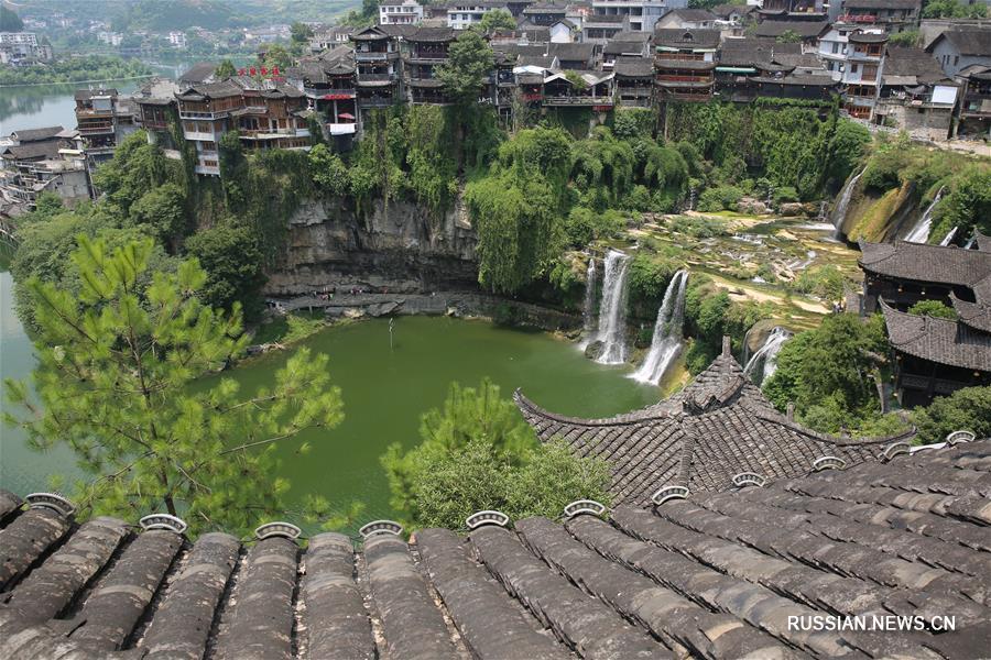Туристы любуются водопадом, наслаждаясь прохладным воздухом на юге Китая