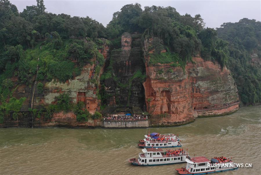 Туристы возле огромной статуи Будды в городском округе Лэшань провинции Сычуань