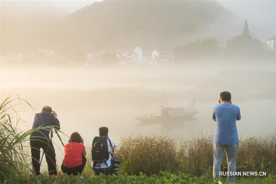 Супруги-рыбаки позируют перед объективами фотокамер в провинции Чжэцзян