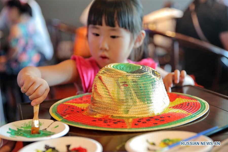 Дети Цзясина раскрашивают соломенные шляпки
